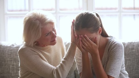 Loving sad old mother sympathizing consoling upset depressed young daughter crying desperate about problem, caring senior mom giving support understanding empathy to stressed adult woman in tears