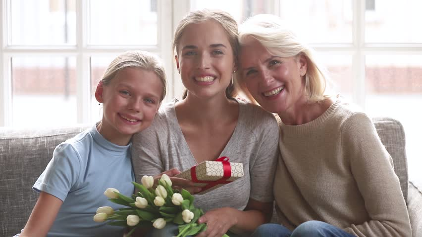 Happy 3 three women age generations family old grandmother and little child daughter congratulating young mom with birthday mothers day presenting flowers gift box bonding together looking at camera
