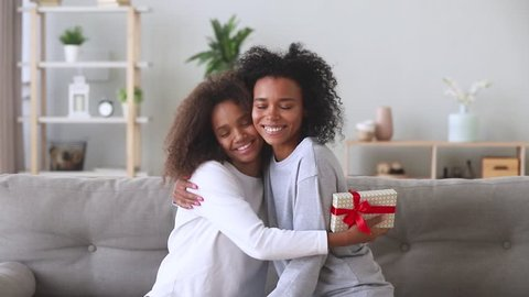 Excited african american teen girl happy to receive gift box from black mother on birthday, loving mum embracing make surprise congratulate teenage daughter hugging give present sit on sofa at home