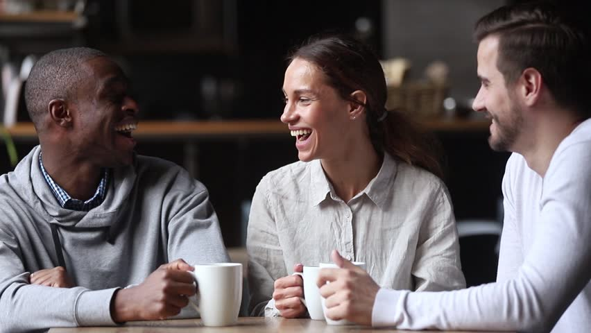 Happy diverse young friends chatting laughing at coffeehouse meeting, multicultural cheerful people group talking sit at cafe table drink coffee tea together, multi-ethnic friendship and fun concept | Shutterstock HD Video #1027488629