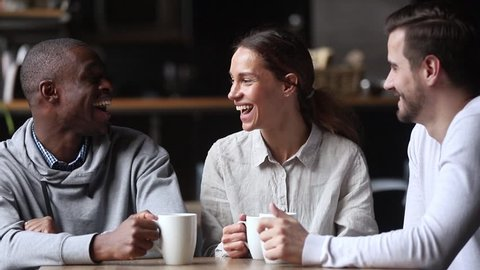 Happy diverse young friends chatting laughing at coffeehouse meeting, multicultural cheerful people group talking sit at cafe table drink coffee tea together, multi-ethnic friendship and fun concept