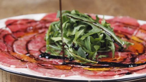 Balsamic vinegar pours on carpaccio in slow motion. Beef carpaccio with arugula and balsamic acusus. A dish stands on a wooden table in a restaurant. Arrangement with a glass of wine and cutlery.