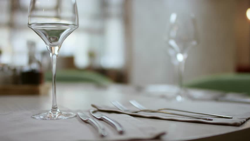 The waiter serves the table in the cafe. Video from the restaurant. The waiter straightens the knife on the table. Table setting. Preparing the restaurant for the opening. decorated table for a dinner | Shutterstock HD Video #1027516739