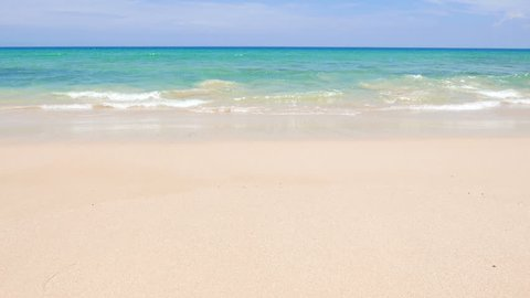 Head-on shot of gentle waves washing ashore a tropical, white-sand beach.