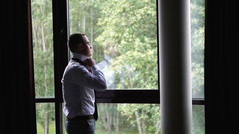Young Man getting ready for a business meeting. Standing in front of the window. Businessman is going to a business lunch. Attractive Man Ties and Ties on a Tie. Groom zips the top button of his shirt