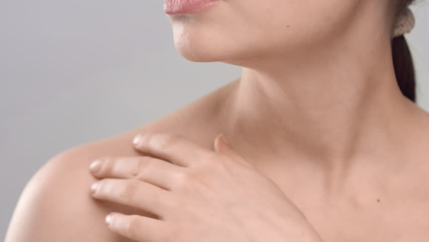 Close-up beauty portrait of young adult woman, that gently strokes her clavicles on light grey background   Skincare concept   Shutterstock HD Video #1027606619