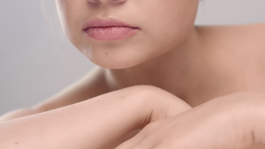 Close-up beauty portrait of young brunette Caucasian woman strokes her neck, tilt her head and looking at camera on grey background | Skincare concept | Shutterstock HD Video #1027606679