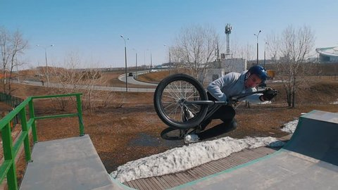 A talanted man on a bicycle performing tricks in the skatepark