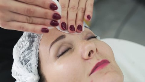 Close up cosmetologist cleans woman skin with wet cotton pads before face care procedure. Girl in beauty salon
