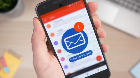 Holding a smartphone and receiving many emails in the Inbox