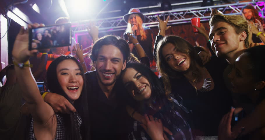 Front view of group of diverse people taking selfie with mobile phone in nightclub. | Shutterstock HD Video #1027637879
