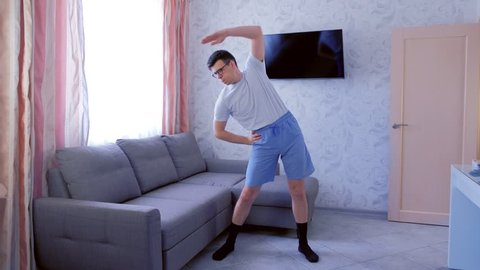 Funny nerd man in glasses and blue shorts is doing complex of fitness exercises at home. Sport humor concept.