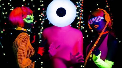 fantastic video of 3 sexy cyber glow ravers filmed in fluorescent clothing under UV black light. 2 cool women and a guy with a circular head
