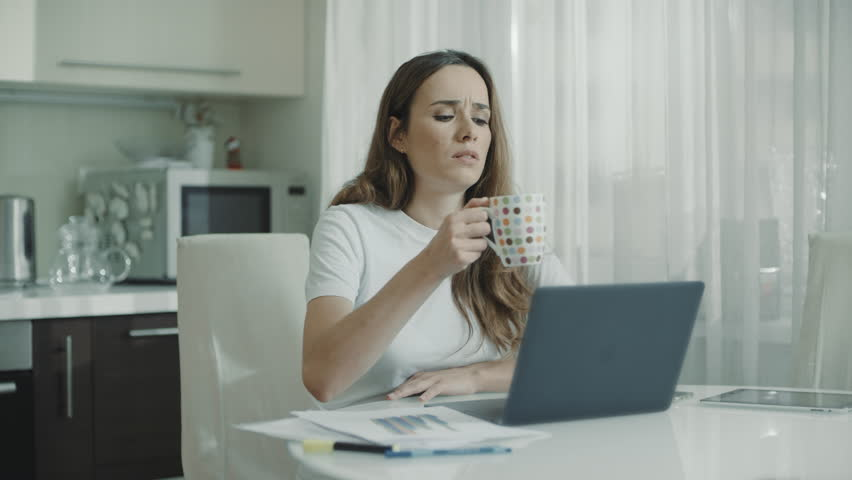 Tired woman using laptop computer at home. Close up of serious woman drinking tea cup on kitchen. Adult student studying online on notebook. Female professional reading news on laptop   Shutterstock HD Video #1027710659