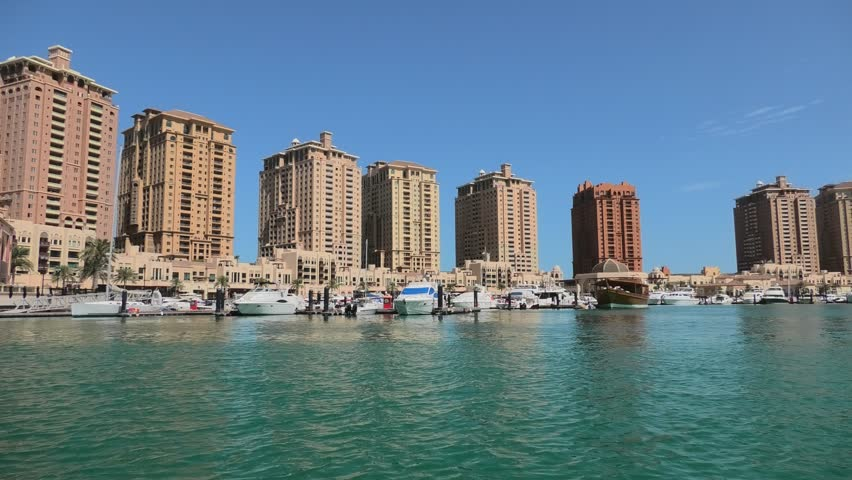Luxurious yachts and boats docked at Porto Arabia Marina. The Pearl-Qatar in Doha is an artificial island icon of the city and a popular tourist destination in Persian Gulf, Middle East.