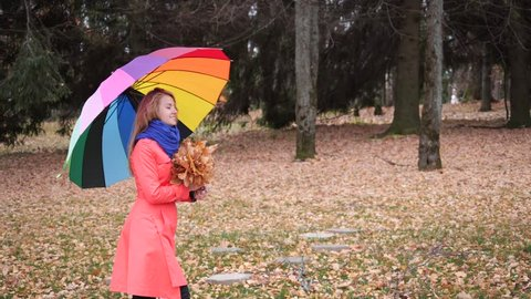 An attractive cute blonde girl in a red coat with yellow maple leaves in her hands happily walks in the autumn forest. Beautiful young woman with colourful umbrella in autumn park.
