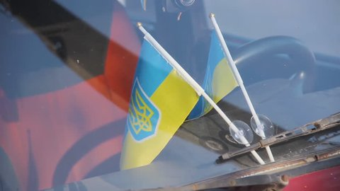 Ukrainian national flags attached to auto windshield glass under car wipers. Old fashioned red colored soviet automobile Zhiguli Vaz Lada in sunny spring day. Ukraine, circa spring 2019