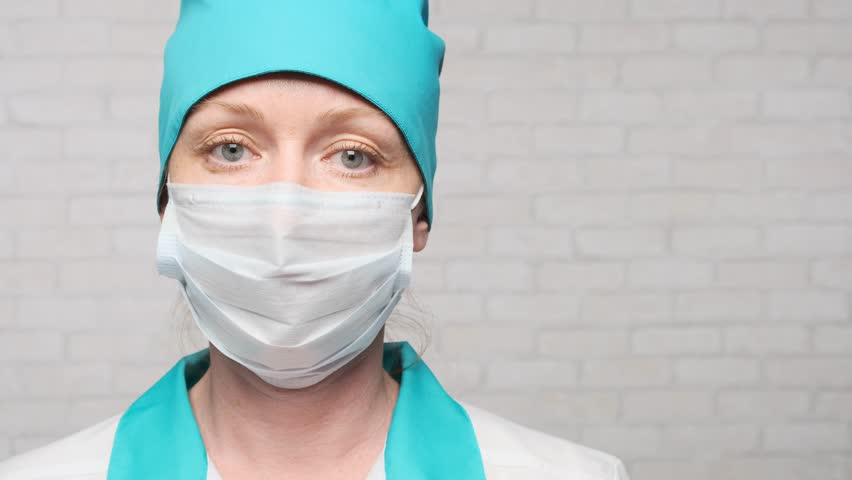Woman doctor inserts a stethoscope into the ears while preparing for the examination of the patient. | Shutterstock HD Video #1027767179