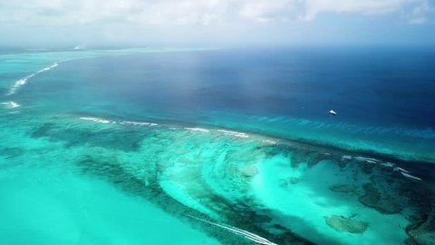 The vast cascading ocean of the Turks and Caicos with the different shades of blue. Filled with multi coloured fish along the coral reef. A great aerial view of the beauty of the islands.