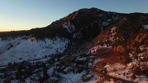 Aerial: Tree Covered Mountains with Snow In Evening Sun in Boulder, Colorado
