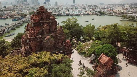 Aerial approach Po Nagar Cham temple red tower Vietnam Nha Trang sunny cityscape. Authentic culture Asia. Modern buildings city bridge active road traffic river fishing old boats. Religion buddhism