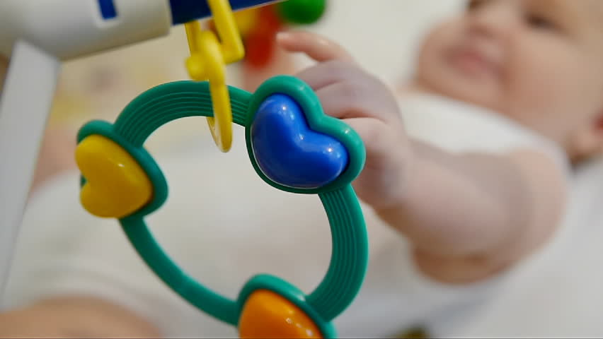 Kid lying on bed with rattle. Infant playing baby rattle.   Shutterstock HD Video #1027931699