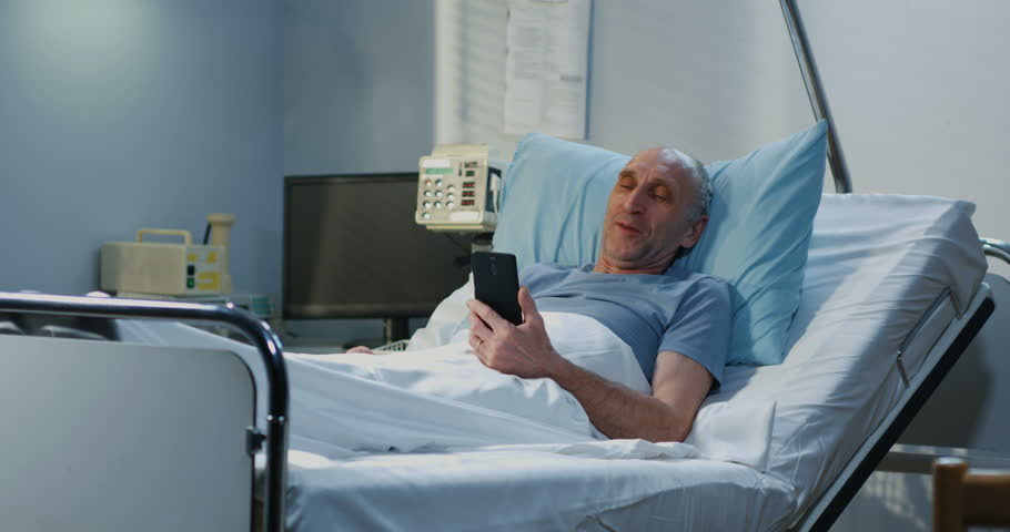Medium shot of senior adult patient using video call in hospital room #1027955789