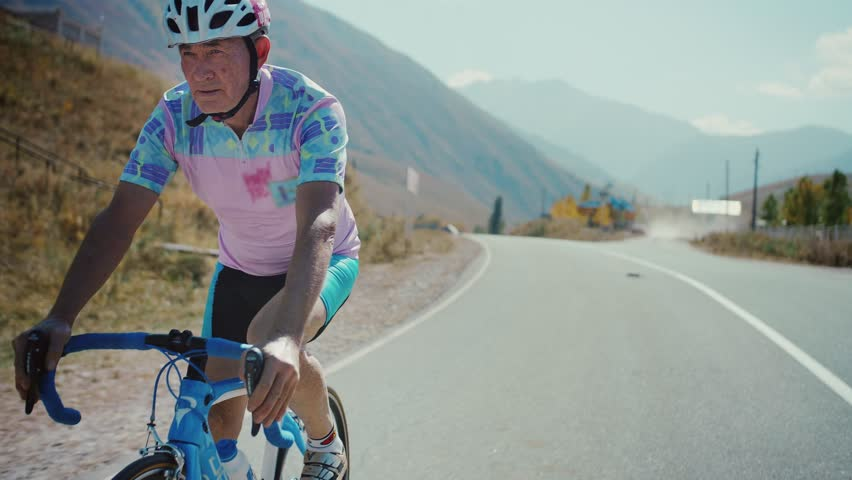 Motivated mature old man or senior is cycling or pedaling in a bicycle in countryside nature during a sunny autumn day enjoying a spot or hobby living a healthy long live wearing a helmet and form