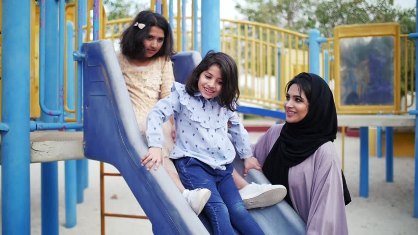 Mom and daughters spending time torgether at the park, playing at the playground and reading stories, Family moments in dubai | Shutterstock HD Video #1027983269