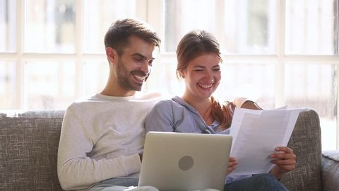 Happy positive young couple holding reading good news in document letter, smiling family checking easy service to pay paper domestic bills online on laptop discuss budget, satisfied with money refund