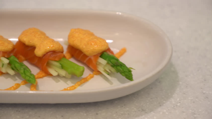 Juicy delicious salmon rolls meal arranged on a white platter plate, sliding shot