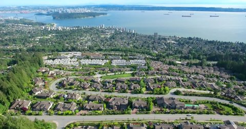VANCOUVER, CANADA. Breathtaking scenery over the residential quarter surrounded by natural wild beauty of British Columbia. Aerial 4K drone view of Vancouver's deepwater harbor.