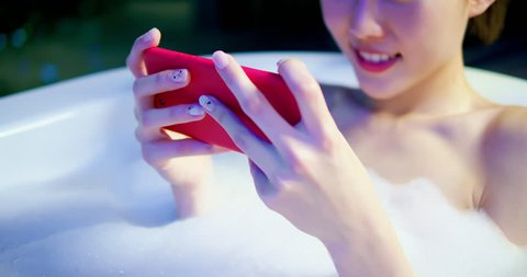 slow motion of woman play mobile game by smart phone happily while bathing at night