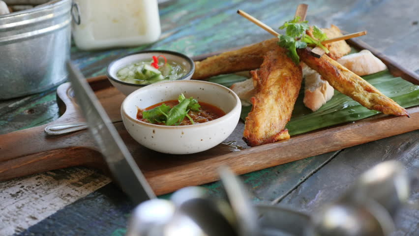 freshly barbecued set of Thai Satay Gai chicken skewers with chili sauce and cucumber garnish on rustic wooden board, vintage wood table street restaurant ambience, daylight, close up pan shot, 50fps