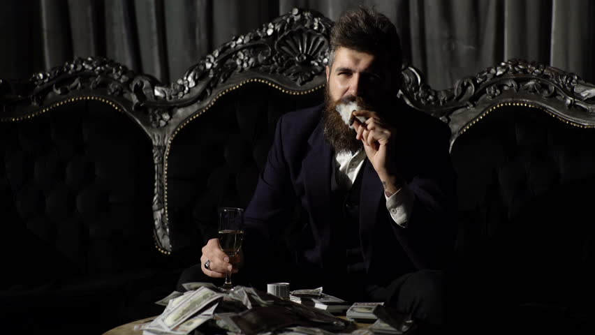 Criminal boss in luxury suit sits on vintage sofa. Crime, mafia, gangster concept. Luxury rich lifestyle.Entrepreneur in elegant suit looks rich. Bearded man champagne glass and smoke cigar