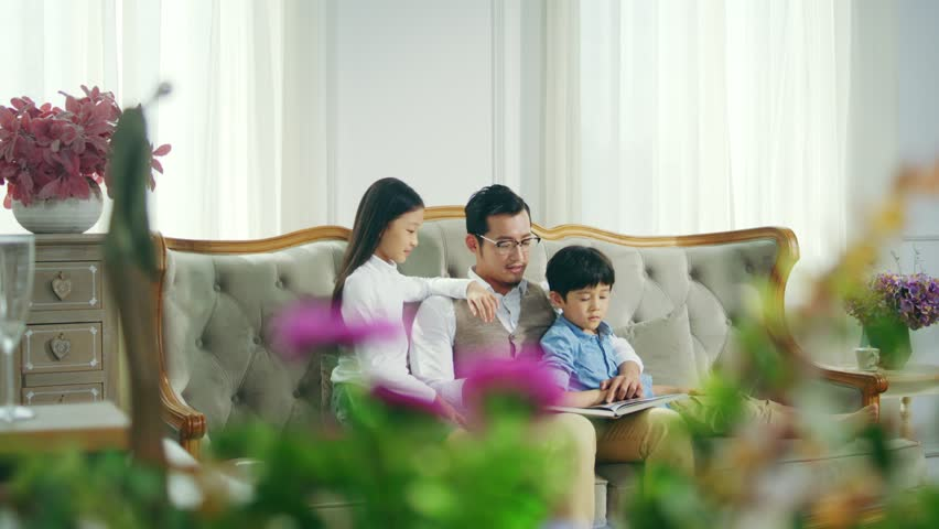 Loving asian father and two children reading book together in living room at home | Shutterstock HD Video #1028057489