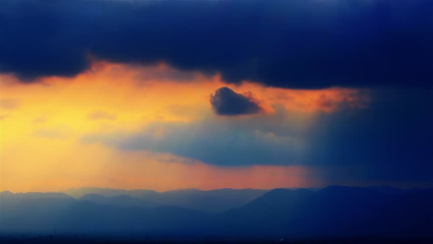 Orange, pink, violet and blue Sunset clouds fast moving over the sky. Dramatic #1028098439