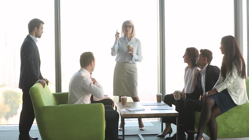 Friendly female mature old leader talking to diverse workers clients group at coffee break, business people team colleagues having fun conversation with middle aged boss discussing work in office | Shutterstock HD Video #1028099159