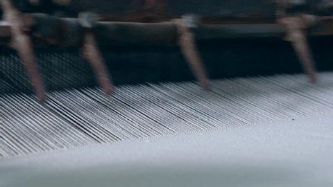 Weaving machine works with white fabric at a textile plant.