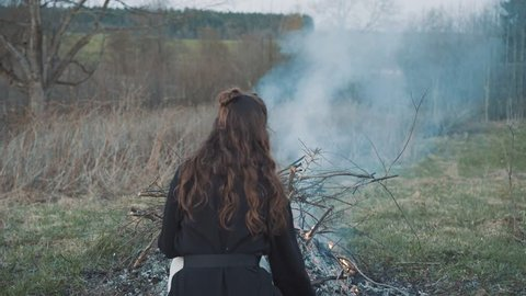 Brunette with long curly hair sits near the bonfire. The first day in the village after the city. Cleansing, calm, comprehension. Who am I. Searching meaning. Warm by  fire. Waste recycling. Relive