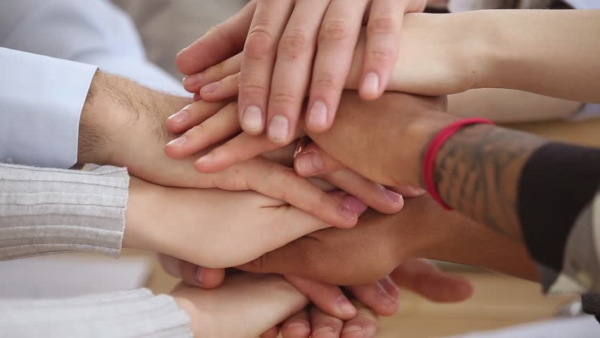 Close up multinational group of people stack hands put palms together, united different ethnicity employees makes common business, students good warm relations, support, trust and teambuilding concept
