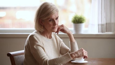 Lonely disappointed elderly blond woman sitting at table with coffee cup lost in sad thoughts feels upset, mature alone melancholic grandma reminiscing relive the past memories regrets in life concept