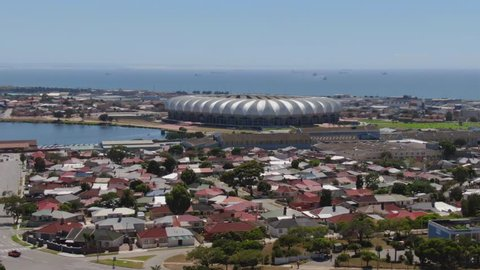 Port Elizabeth, South Africa - circa 2010s: Aerial jib up, reveal suburban houses, Nelson Mandela Bay Stadium, North End Lake, industrial area and ships at sea waiting to enter harbour
