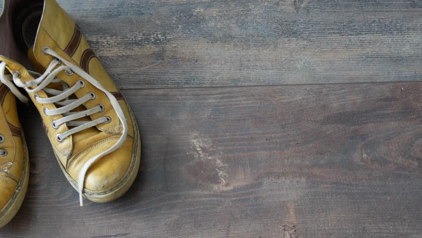 Pair of yellow used shoes | Shutterstock HD Video #1028159759