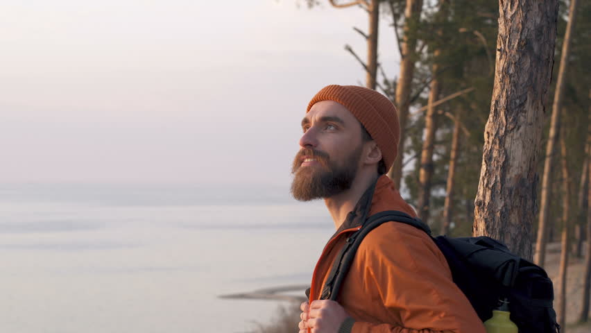 Portrait of travel beard man with backpack outdoors. Looking around and enjoying nie day.