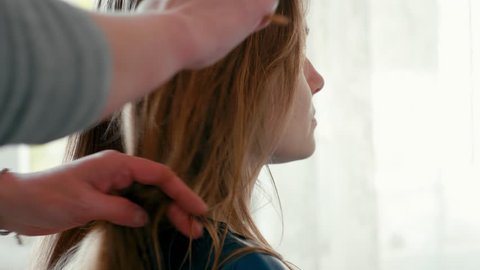 Close-Up Shot of Hairdresser's Hands Combing with Hairbrush the Female Client's Wet Straight Hair, Preparing and Getting Ready to make a Haircut in Beauty Salon. Slow motion 4K Static Video