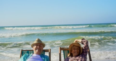 Front view of active senior Caucasian couple having fun on a sun lounger at beach. They are relaxing on a sun lounger 4k