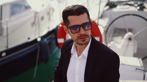 Young handsome man on a yacht. Serious businessman in sunglasses in a suit. Stylish modern guy on deck topside with lifebuoy. Luxury VIP model sitting