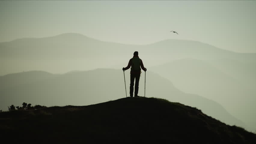 Silhouette of Caucasian European female adventure hiker on her hiking expedition outdoor Snowdonia National Park Wales RED MONSTRO #1028326139