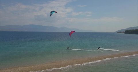 Two kitesurfers somewhere in Greece, with an isolated boat. Riding blue water.